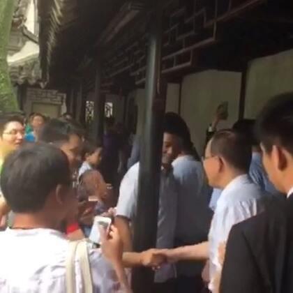 正在苏州拙政园访问的秘书长潘基文与游客们握手寒暄。